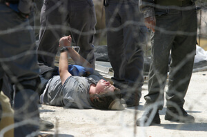 Arrested Jewish settler lies on the roof of synagogue during evacuation of the northern West Bank ...